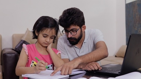 Young father helping his daughter in studies while working on a laptop