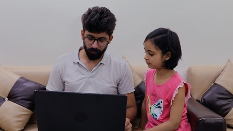 A modern father teaching his young girl how to use a laptop