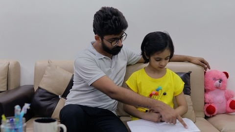 Indian father checking his school-age daughter's homework in a notebook