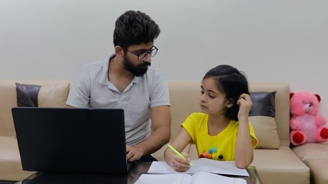 Modern Indian father on a laptop helping his little daughter in studies