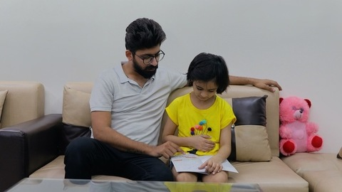 Indian father helping his little daughter in studies - happy parenting