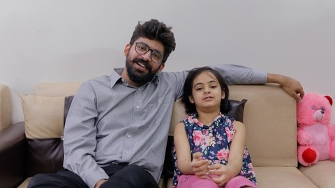 Indian father-daughter happily enjoying their free time together and watching tv