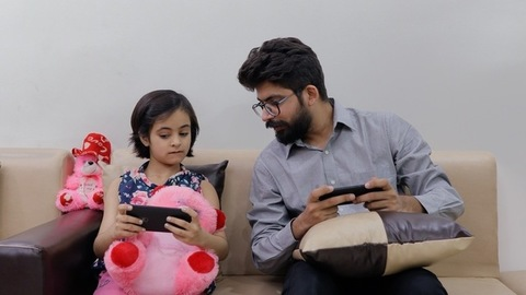 Father-daughter duo playing games on their smartphones during free time