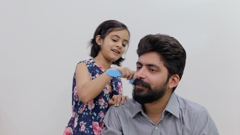 The little girl helping her dad to groom by combing his beard - father-child bonding