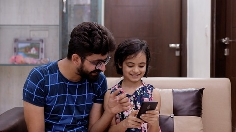 Father helping daughter in online shopping on mobile - Technology adoption by kids