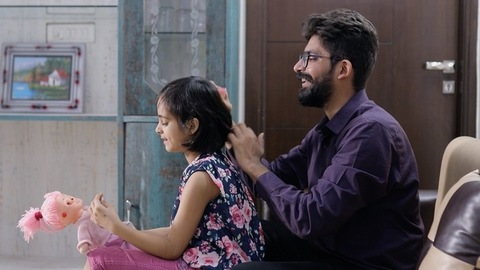 Caring father combing his daughter's hair at home - Modern Indian Lifestyle