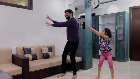 Handsome Indian dad practicing dance with his girl - happy family time