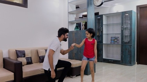 Indian daughter spins around holding her dad's finger and enjoys free time