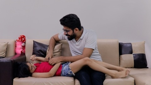Indian dad having a fun time with his little girl on a sofa - father-child bonding