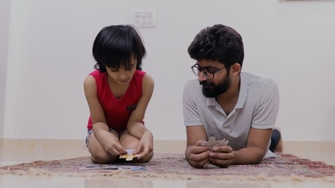 Single father and daughter playing fun games while lying down on a carpet