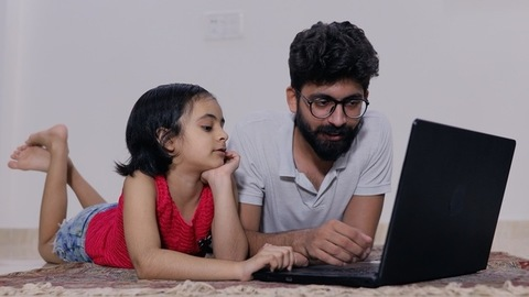 Indian father teaching his little daughter on the laptop - modern teaching concept