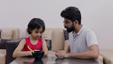 An Indian father in the living room is upset with his daughter for not eating food