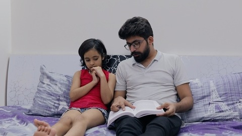 Modern father teaching his little daughter from a book - urban lifestyle concept