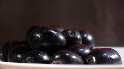Popular fruits Indian blackberries kept on a plate rotating on a turntable. Indian summer fruit