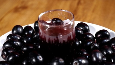 A few black Jamuns falling into a transparent glass of juice - a tasty drink. Indian summer fruit