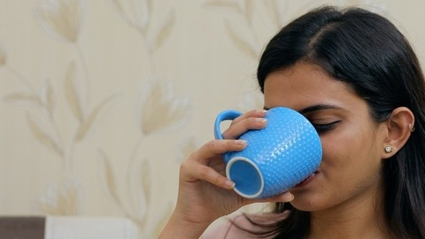Relaxed Indian female drinking a delicious beverage while sitting in the living room