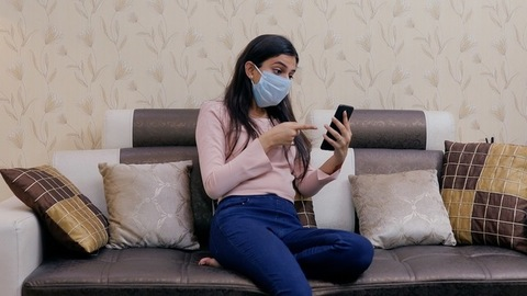 Sick Indian female in a surgical mask busy over a video call - lifestyle concept