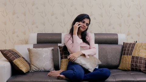 Pretty Indian female calling someone from her mobile while sitting on a couch