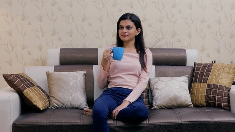 Medium shot of a young woman enjoying a cup of tea or coffee in the evening