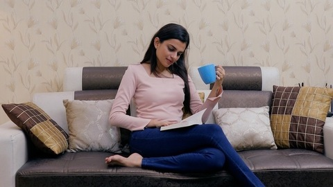 Beautiful Indian girl spending leisure time in reading her favorite novel at home
