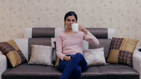 The attractive young girl happily watching television at home during leisure time