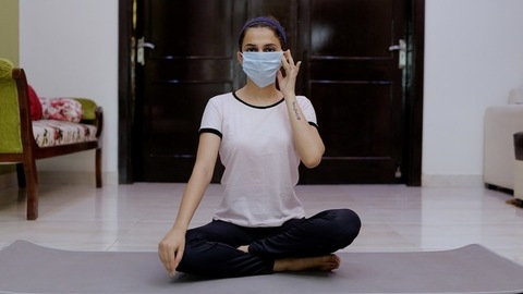 Beautiful young female taking a sigh of relief after removing her surgical mask