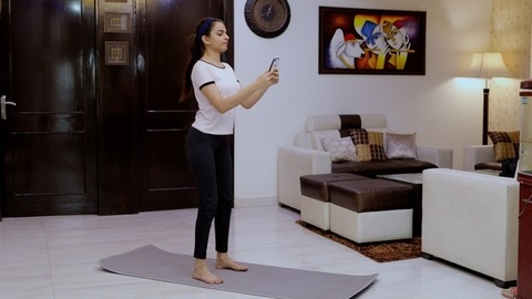Beautiful Indian female doing squats on a fitness mat - healthy lifestyle concept