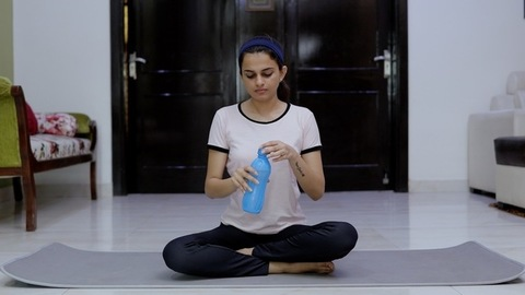 Sportswoman drinking water after the yoga session - healthy lifestyle concept