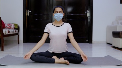 Indian girl meditating in Ardhasan (half-lotus pose) for a healthy lifestyle