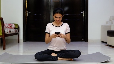 A beautiful young girl happily using her mobile phone after her yoga session