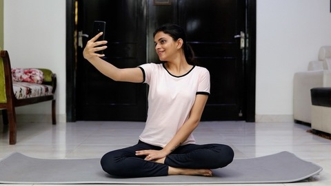Pretty Indian girl sitting on a yoga mat and taking selfies from her smartphone