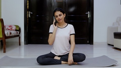 A beautiful Indian girl is interrupted by a phone call during the meditation