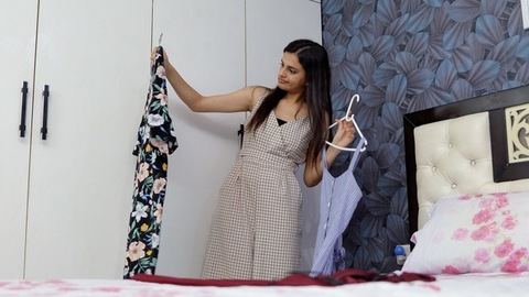 A beautiful Indian girl is confused about what clothes to wear for the holiday