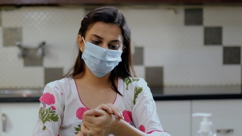 Young female disinfecting her hands using sanitizer while wearing a surgical mask