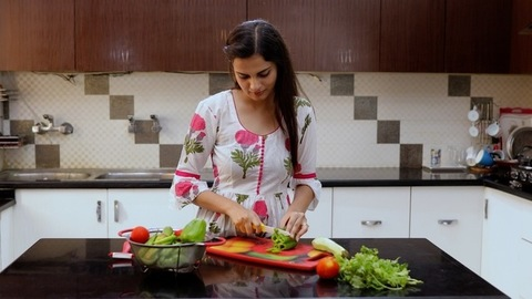 Medium shot of beautiful Indian female chopping vegetables in the kitchen