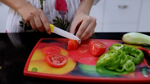 Woman hands slicing tomato and capsicum using a knife on a chopping board