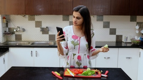 The attractive young girl using her touchscreen mobile phone in the home kitchen