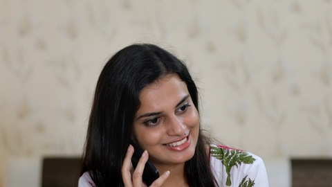 Pretty Indian female calling someone from her smartphone - blurred background