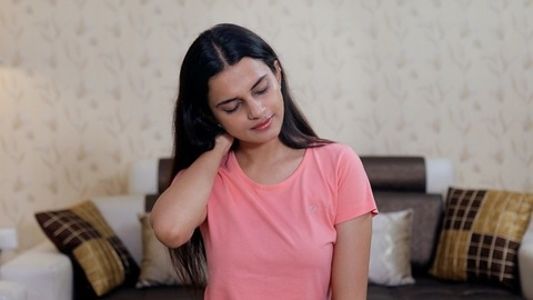 Pretty Indian girl suffering from severe neck pain - health and medical concept