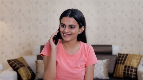 A beautiful young girl happily talking to her friend on a phone call - leisure time