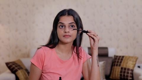 Medium shot of young Indian girl applying mascara on her eyelashes - makeup concept