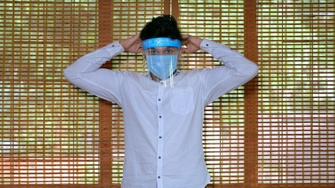 Medium shot of a young guy wearing a medical mask and protective face shield