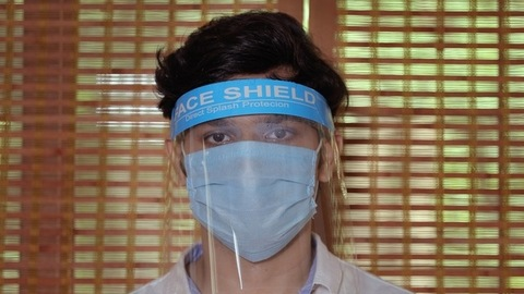 Closeup shot of a young guy wearing a medical mask and protective face shield