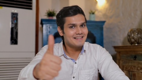 Attractive young teenager showing a thumbs-up while smiling towards the camera