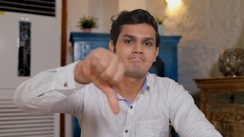 Handsome Indian guy shows a thumbs down gesture while looking at the camera