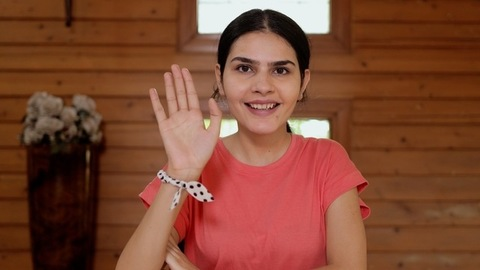 Attractive Indian female doing a hello gesture while looking towards the camera