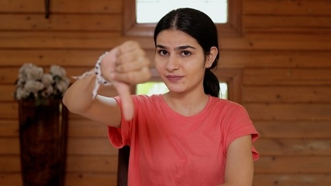 Pretty Indian girl shows a thumbs down gesture while looking towards the camera