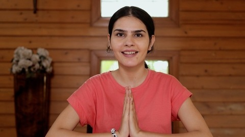 Portrait shot of an Indian girl doing namaste gesture while looking at the camera