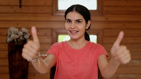 Portrait of a pretty Indian girl smiling and gesturing thumbs-ups at the camera
