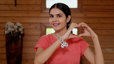 Portrait of a pretty Indian girl smiling and making a heart shape with her hands